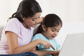 Woman helping her daughter to use a laptop — Stock Photo