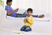 Boy holding felt tip pen with father using cell phone — Stock Photo