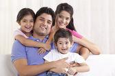 Happy family sitting on sofa — Stock Photo