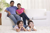 Happy family sitting on sofa — Stock Photo