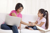Woman working on laptop while daughter drawing — Stock Photo