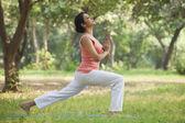 Woman doing yoga in lawn — Stock Photo