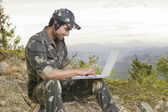 Young soldier using laptop — Stock Photo
