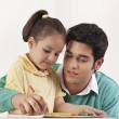 Father helping her daughter in drawing — Stock Photo #46482573