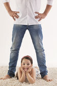 Cute girl lying between father's legs — Stockfoto