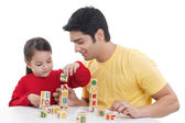 Smiling girl and man holding dollhouse — Stock Photo