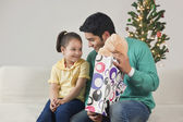 Cute girl with father holding gift — Stock Photo
