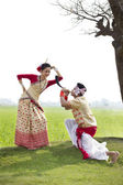 Bihu man blowing on a pepa and Bihu woman dances — Stock Photo