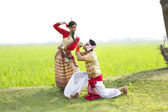 Bihu man blowing on a pepa and Bihu woman dances — Stock Photo