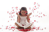 Rose petals falling on a little girl — Stock Photo