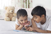 Cute siblings reading book in bed — Stock Photo