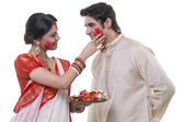 Bengali woman putting sindoor on man's face — Stock Photo