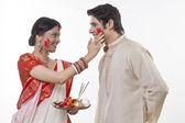 Bengali woman putting sindoor on man's face — Stock Photo