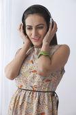 Beautiful young woman listening to headphones — Fotografia Stock