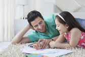 Father assisting girl in drawing — Stock Photo