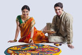 Maharashtrian couple placing diyas on rangoli — Stock Photo