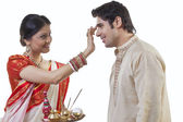 Bengali woman putting tika on man's head — Stock Photo