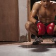 Tired male boxer crouching in gym — Stock Photo #51109801