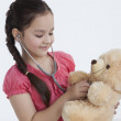 Little girl playing doctor with teddy bear — Stock Photo #51109899