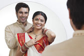 Bengali man tying necklace around wife's neck — Stock Photo