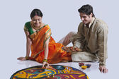 Maharashtrian couple placing diyas on rangoli — Stock Photo