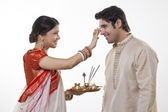 Bengali woman putting tika on man's head — Stock Photo