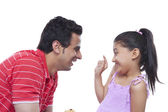 Playful daughter putting cream on father's nose — Stock Photo