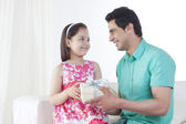 Little girl giving gift box to father in house — Stock Photo