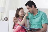 Father and daughter reading story book — Stock Photo