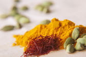 Green cardamom pods, saffron and turmeric powder — Stock Photo