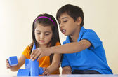 Brother and sister stacking geometric shapes — Stock Photo