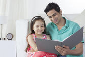 Happy father and daughter reading story book — Stock Photo