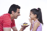 Happy father giving donut to daughter — Stock Photo