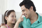 Little girl touching father's nose at home — Stock Photo