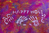 Handprints with text Happy Holi written on rangoli — Stock Photo