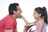Happy daughter feeding donut to father — Stock Photo