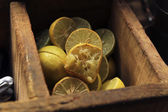 Halved lemons in wooden container — Stock Photo
