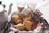 Fresh samosas with tea glasses on table — Stock Photo