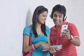 Friends reading text message on smart phone — ストック写真