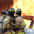 Firemen extinguishing a car fire — Stock Photo