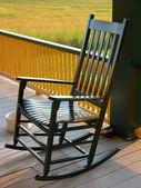 Schommelstoel in geel op de veranda — Stockfoto