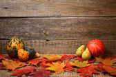 Autumn abstraction. Leaves and pumpkins on the old wooden background. — Stock Photo