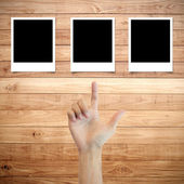 Polaroid photo frame on wood background with hand finger directi — Stock Photo