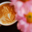 White cup of coffee with pink flower on black — Stock Photo #18998931