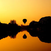 Hot Air Balloon at Sunrise on the river — Stock Photo
