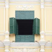 The opened green window on the yellow wall green window — Stock Photo