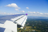 View of jet plane wing with city view — Stockfoto