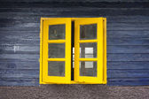 Texture of bright painted wooden wall with yellow closed window — Stock Photo
