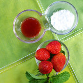 Strawberries in the bowl with green fabric — Stock Photo
