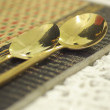 Close up gold spoon on dining table restaurant — Stock Photo #26412591